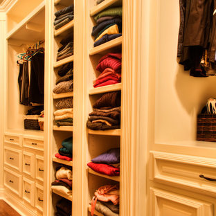 Walk-in closet - craftsman gender-neutral medium tone wood floor walk-in closet idea in Other with raised-panel cabinets and white cabinets