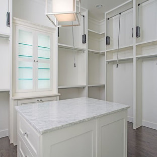 This is an example of a large contemporary gender-neutral walk-in wardrobe in Dallas with shaker cabinets, white cabinets and dark hardwood floors.