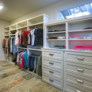 Photo of a large contemporary gender neutral dressing room in Austin with shaker cabinets, beige cabinets and slate flooring.