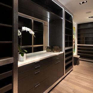 Ispirazione per un'ampia cabina armadio per uomo design con ante marroni, pavimento in legno massello medio e ante lisce