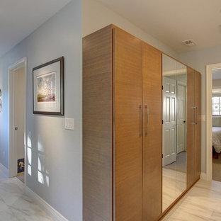 Foto de armario unisex, clásico renovado, de tamaño medio, con armarios con paneles lisos, puertas de armario de madera oscura, suelo de mármol y suelo gris