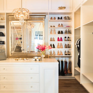 Design ideas for a transitional women's storage and wardrobe in Los Angeles with white cabinets and brown floor.