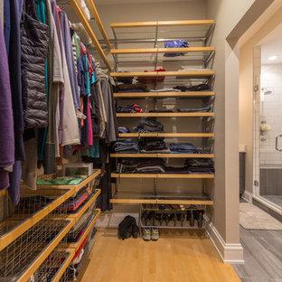 Imagen de armario vestidor unisex, clásico, de tamaño medio, con armarios abiertos, puertas de armario de madera oscura y suelo de madera en tonos medios