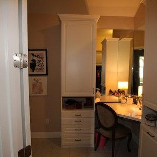 Ejemplo de armario vestidor de mujer, de tamaño medio, con armarios con paneles con relieve, puertas de armario blancas y suelo de baldosas de terracota
