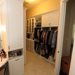 Imagen de armario vestidor de mujer, de tamaño medio, con armarios con paneles con relieve, puertas de armario blancas y suelo de baldosas de terracota