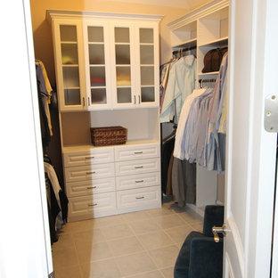 Cette image montre un dressing de taille moyenne pour un homme avec un placard avec porte à panneau surélevé, des portes de placard blanches et un sol en carreau de terre cuite.