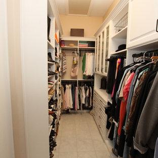 Modelo de armario vestidor de mujer, de tamaño medio, con armarios con paneles con relieve, puertas de armario blancas y suelo de baldosas de terracota