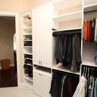 Diseño de armario vestidor de hombre, de tamaño medio, con armarios con paneles con relieve, puertas de armario blancas y suelo de baldosas de terracota