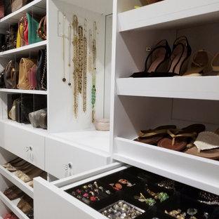 Imagen de armario vestidor de mujer, moderno, de tamaño medio, con armarios con paneles lisos, puertas de armario blancas y suelo de mármol
