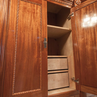 Inspiration for an expansive classic walk-in wardrobe for women in San Diego with beaded cabinets, medium wood cabinets and travertine flooring.