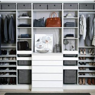 Modelo de vestidor unisex, minimalista, grande, con armarios con paneles lisos, puertas de armario blancas, suelo de madera clara y suelo beige