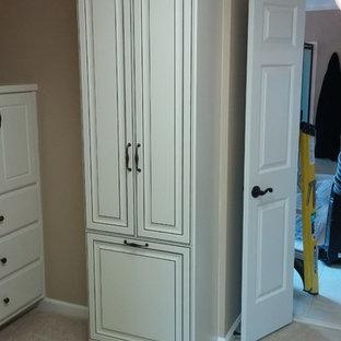 Foto de armario vestidor unisex, clásico, de tamaño medio, con armarios con paneles con relieve, puertas de armario con efecto envejecido, moqueta y suelo beige