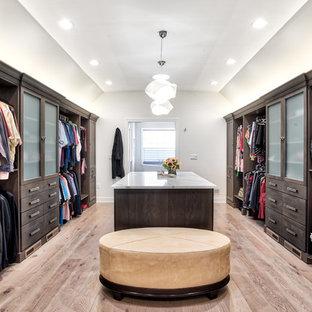Ispirazione per un'ampia cabina armadio unisex classica con ante lisce, ante in legno bruno e parquet chiaro