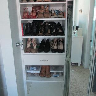Foto de armario unisex, costero, de tamaño medio, con armarios con paneles lisos, puertas de armario blancas, moqueta y suelo beige