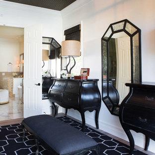 Ejemplo de vestidor de hombre, mediterráneo, grande, con armarios con paneles con relieve, puertas de armario negras y suelo de madera en tonos medios