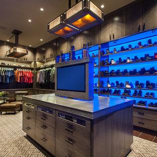 Ejemplo de armario vestidor de hombre, rural, extra grande, con armarios con paneles lisos, puertas de armario con efecto envejecido, moqueta y suelo marrón