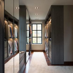 Inredning av ett modernt mycket stort walk-in-closet för män, med släta luckor, heltäckningsmatta, beiget golv och grå skåp
