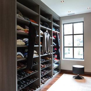 Imagen de armario vestidor de hombre, actual, extra grande, con armarios con paneles lisos, puertas de armario de madera oscura, moqueta y suelo beige