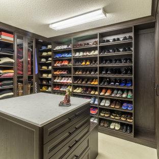 Modelo de armario vestidor de hombre, contemporáneo, grande, con armarios con paneles empotrados, puertas de armario de madera en tonos medios y moqueta