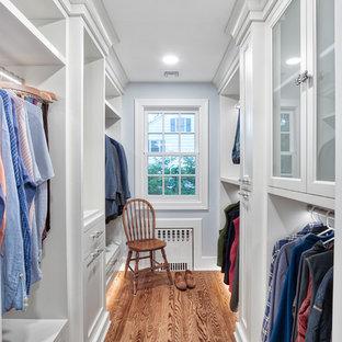 Imagen de armario vestidor de hombre, clásico, extra grande, con armarios con rebordes decorativos, puertas de armario blancas y suelo de madera en tonos medios
