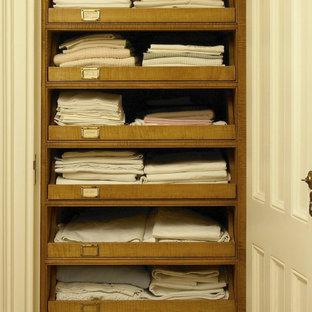 Esempio di un piccolo armadio o armadio a muro tradizionale con ante in legno chiaro e pavimento in legno massello medio