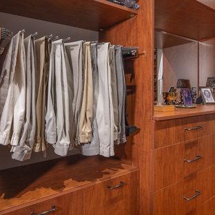 Diseño de armario vestidor unisex, de estilo de casa de campo, grande, con armarios con paneles lisos, puertas de armario de madera oscura y suelo de madera en tonos medios