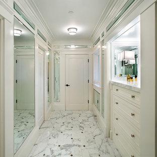 Imagen de armario y vestidor mediterráneo con armarios con rebordes decorativos, puertas de armario blancas y suelo de mármol