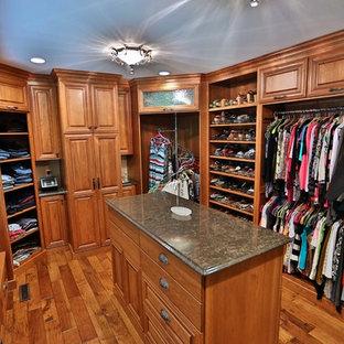 Diseño de armario vestidor unisex, tradicional, grande, con armarios con paneles con relieve, puertas de armario de madera oscura y suelo de madera en tonos medios
