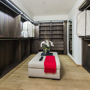 Large modern gender-neutral walk-in wardrobe in Los Angeles with open cabinets, dark wood cabinets and light hardwood floors.