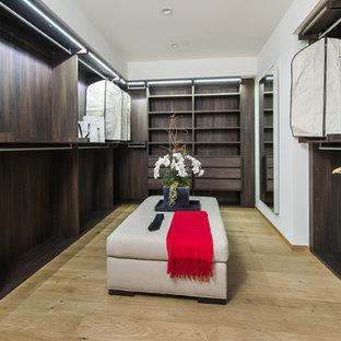 Exempel på ett stort modernt walk-in-closet för könsneutrala, med öppna hyllor, skåp i mörkt trä och ljust trägolv