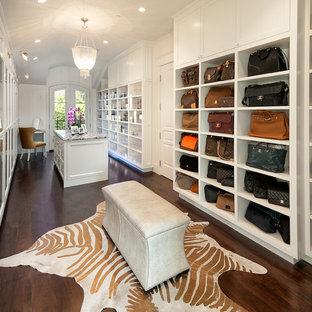 Exemple d'un grand dressing room chic pour une femme avec un placard sans porte, des portes de placard blanches, un sol en bois foncé et un sol marron.