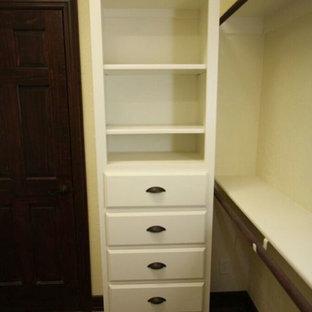 Diseño de armario vestidor unisex, tradicional, pequeño, con armarios abiertos, puertas de armario blancas, suelo de madera en tonos medios y suelo marrón