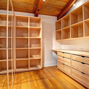 Photo of a contemporary storage and wardrobe in San Diego with open cabinets and light wood cabinets.