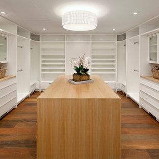 Idée de décoration pour un dressing minimaliste neutre avec un placard sans porte, des portes de placard blanches, un sol en bois brun et un sol marron.