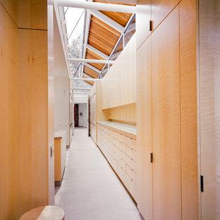 Modernes Ankleidezimmer mit flächenbündigen Schrankfronten, hellen Holzschränken und Kalkstein in Miami