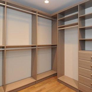 Idées déco pour un dressing classique neutre avec un placard à porte plane, des portes de placard marrons, un sol en bois clair et un sol orange.