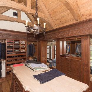 Ejemplo de armario vestidor de mujer, mediterráneo, grande, con armarios con paneles empotrados, puertas de armario beige, suelo de madera oscura y suelo blanco