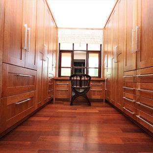 他の地域の大きい男女兼用エクレクティックスタイルのおしゃれなウォークインクローゼット (フラットパネル扉のキャビネット、中間色木目調キャビネット、ラミネートの床、茶色い床) の写真
