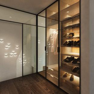Modelo de armario vestidor de hombre, minimalista, de tamaño medio, con armarios tipo vitrina, puertas de armario de madera en tonos medios y suelo de madera oscura