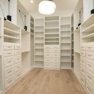 Foto de armario vestidor unisex, campestre, grande, con armarios estilo shaker, puertas de armario blancas y suelo de madera clara