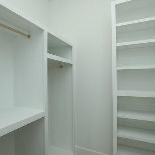 Foto de armario vestidor unisex, de estilo de casa de campo, grande, con armarios estilo shaker, puertas de armario blancas y suelo de madera clara