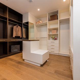 Foto de armario y vestidor unisex, clásico, de tamaño medio, con armarios con paneles lisos, puertas de armario blancas, suelo de madera en tonos medios y suelo marrón