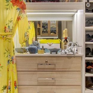 Ejemplo de armario vestidor de mujer, actual, de tamaño medio, con armarios con paneles lisos, puertas de armario de madera clara, moqueta y suelo beige