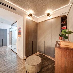 Idee per un piccolo spazio per vestirsi unisex minimalista con ante lisce, ante marroni, pavimento in laminato e pavimento marrone