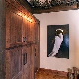 Ispirazione per uno spazio per vestirsi unisex industriale con ante con riquadro incassato, ante in legno bruno e pavimento in legno massello medio