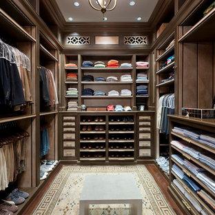 На фото: большая гардеробная комната в классическом стиле с открытыми фасадами, темными деревянными фасадами и темным паркетным полом для мужчин с