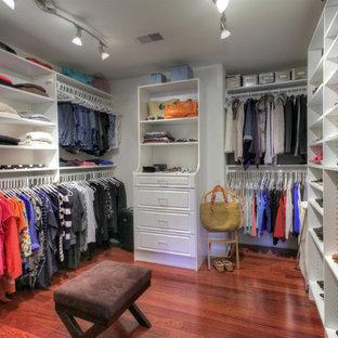 Imagen de armario vestidor de mujer, bohemio, con armarios con paneles con relieve, puertas de armario blancas y suelo de madera oscura