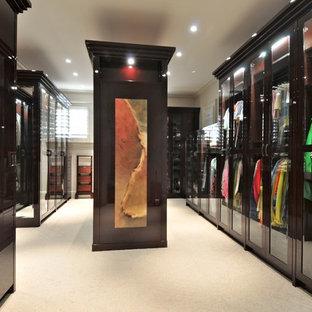 Ispirazione per un'ampia cabina armadio unisex contemporanea con ante di vetro, ante in legno bruno e moquette