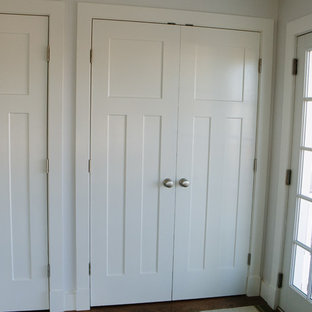 This is an example of a beach style gender-neutral built-in wardrobe in Providence with recessed-panel cabinets, white cabinets and medium hardwood floors.