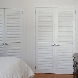 Inspiration for a mid-sized traditional gender-neutral built-in wardrobe in Toronto with louvered cabinets, white cabinets, medium hardwood floors and brown floor.